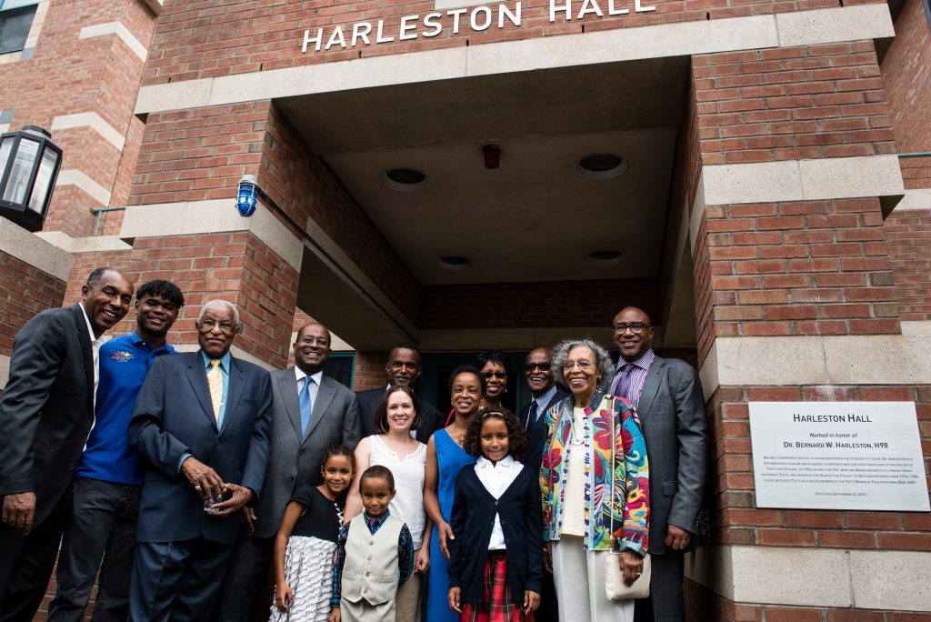 09/23/2016 - Medford/Somerville, Mass. - Dr. Bernard W. Harleston, H98, and his wife Marie pose with family members near the commemorative plaque during the official dedication of Harleston Hall, formerly South Hall, on September 23, 2016. Dr. Harleston, a psychologist, was the first African American hired to a tenure-track position at Tufts and the first African American president of the City College of New York. He is a trustee emeritus of Tufts, having served on the board from 2002 to 2007. (Alonso Nichols/Tufts University)