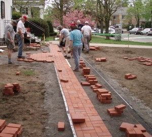 "Buildings and Grounds Action Team laying a new brick ""dedication"" sidewalk."